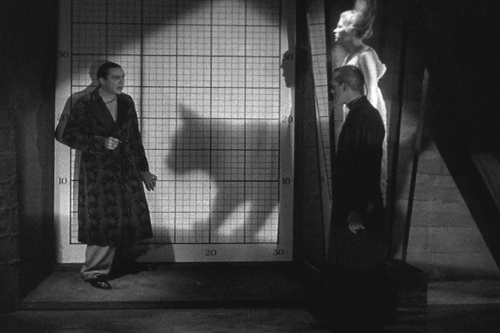 The confrontation between Belau Lugosi (left) and Boris Karloff (right) is interrupted by the shadow of the titular BLACK CAT