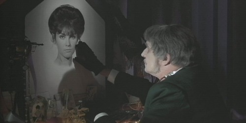 Phibes (Vincent Price) gazes upon a photograph of his late wife Victoria (Caroline Munro).