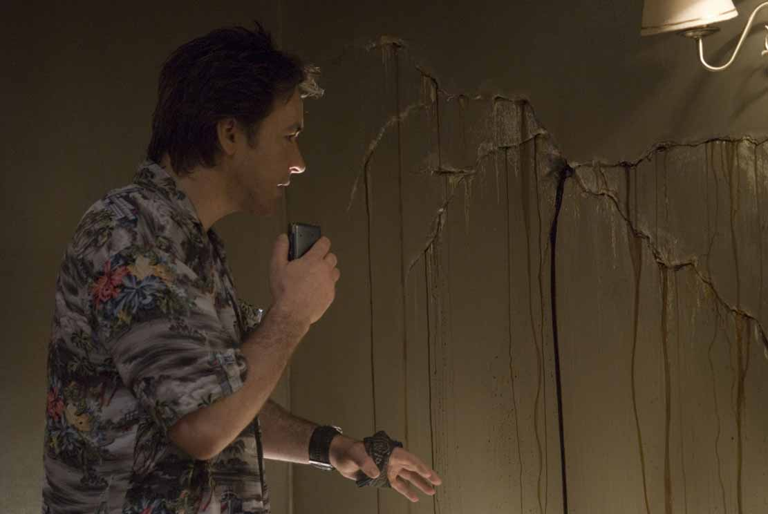 Bleeding cracks in the wall crack the the wall of Mike Enslin (John Cusack)'s skepticism.