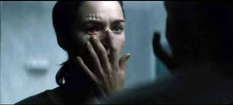 Gina McVey (Lena Headey) is observed by her reflection.