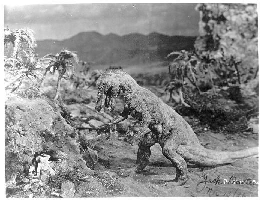A split screen effect combines live human actors with stop-motion dinosaurs in ths publicity still.